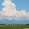 写真: 夏の雲・・・田んぼと山に乗って