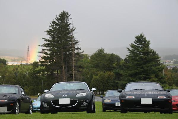 ロードスター達の後ろに太い虹が光る